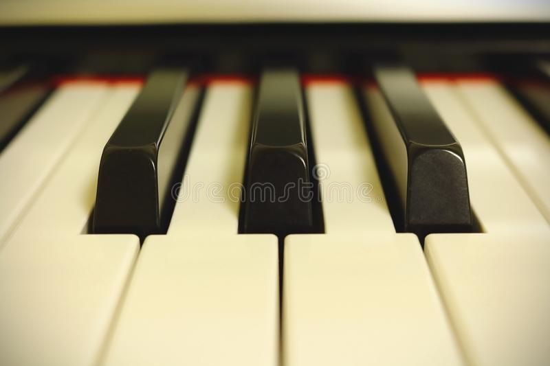 Light piano keyboard close up in white light. Light piano keyboard close up in bright white light, music, sound, synthesizer, equipment, instrument, black stock image