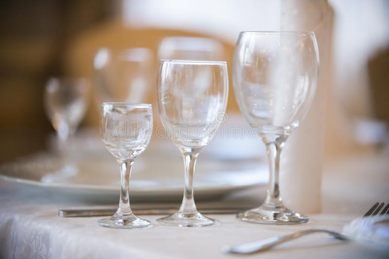 Light picture of empty glasses in restaurant - white plates. Mid shot stock image