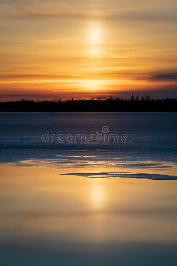 Light pillar in sunset reflecting from melting lake water. Landscape royalty free stock photography