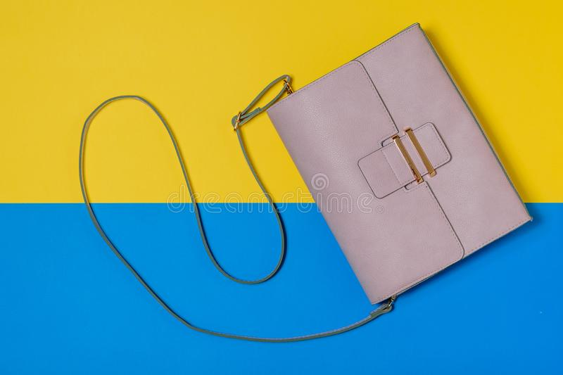 Light pink women`s bag on yellow and blue background. Modern women`s leather accessory. The view from the top stock photo
