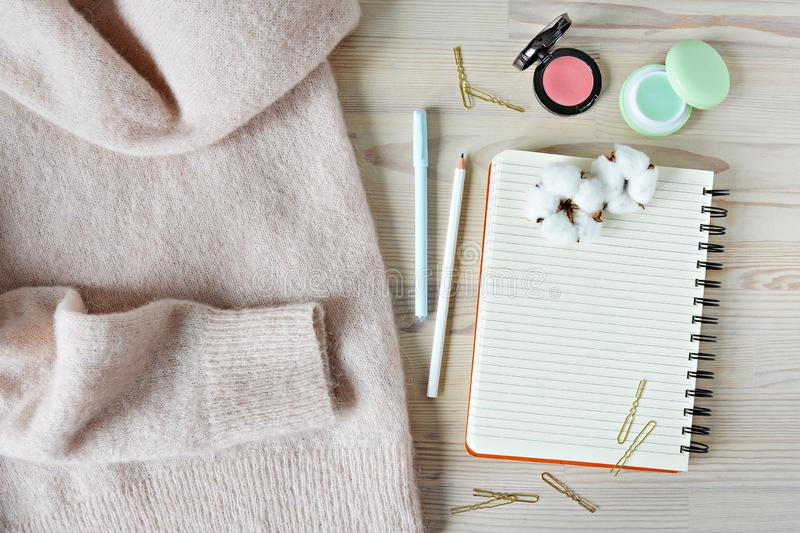 Light pink wool sweater, black spiral notebook, mint pen, white pencil, golden hairpins, pink blush, lip balm and cotton flowers. Light pink wool sweater, black royalty free stock photos