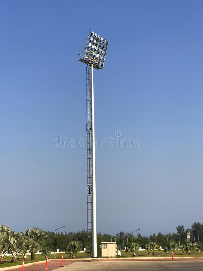 Light pole tower in field on blue sky. Big light pole tower in field on blue sky. There are many spotlight beside field. and many plants around the field royalty free stock photo
