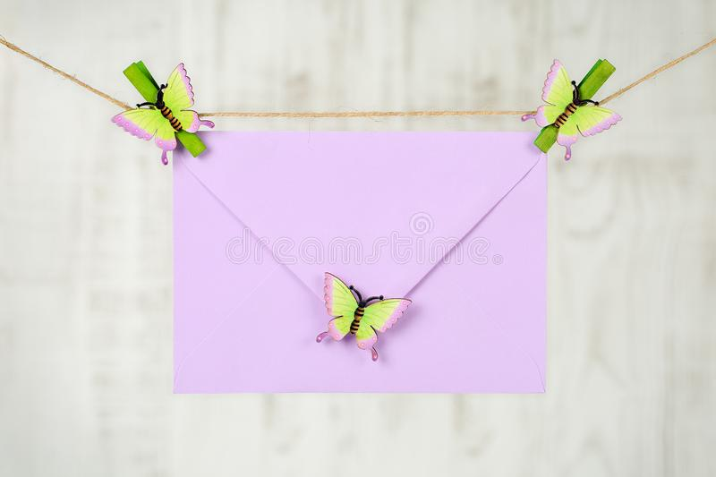 Light purple envelope from recycled paper hanging on a jute twine with green clothes pins with decorative butterflies. Hello stock photo
