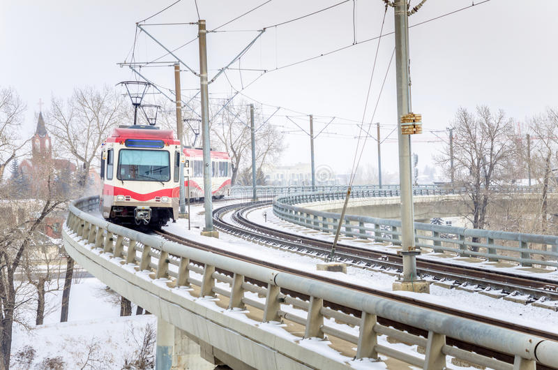 Light Rail Train on a Curving Bridge on a Snowy Winter Day. Light Rail Train on a Bridge Covered in Snow in Calgary on a Winter Day stock images