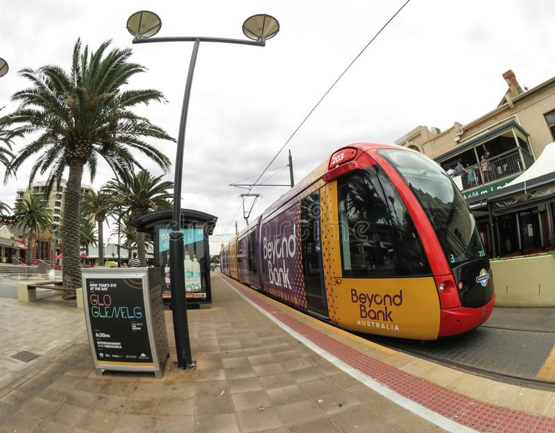 Light rail train stopping at Glenelg beach station in the cloudy day. royalty free stock photo