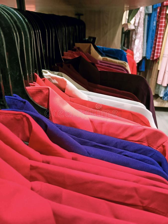 Light red, blue, white and different colours of formal shirt in a shopping mall for sale.  stock photography