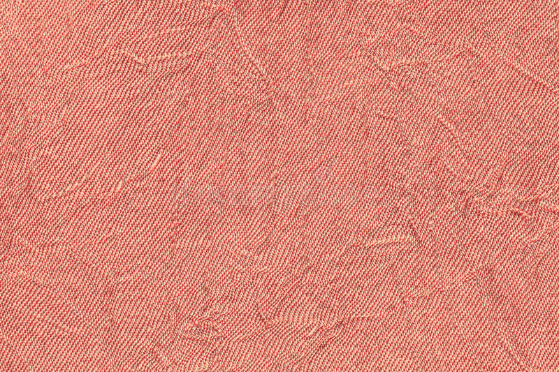 Light red wavy background from a textile material. Fabric with fold texture closeup. Creased shiny coral cloth stock images