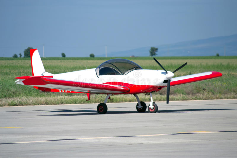 Light red/white painted private aircraft. A light single-engine aircraft royalty free stock photography