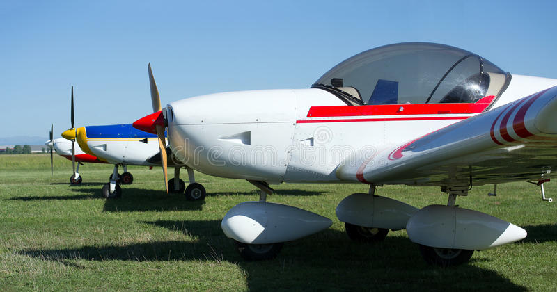 Three light aircrafts. Standing next to each other on the grass runway stock image