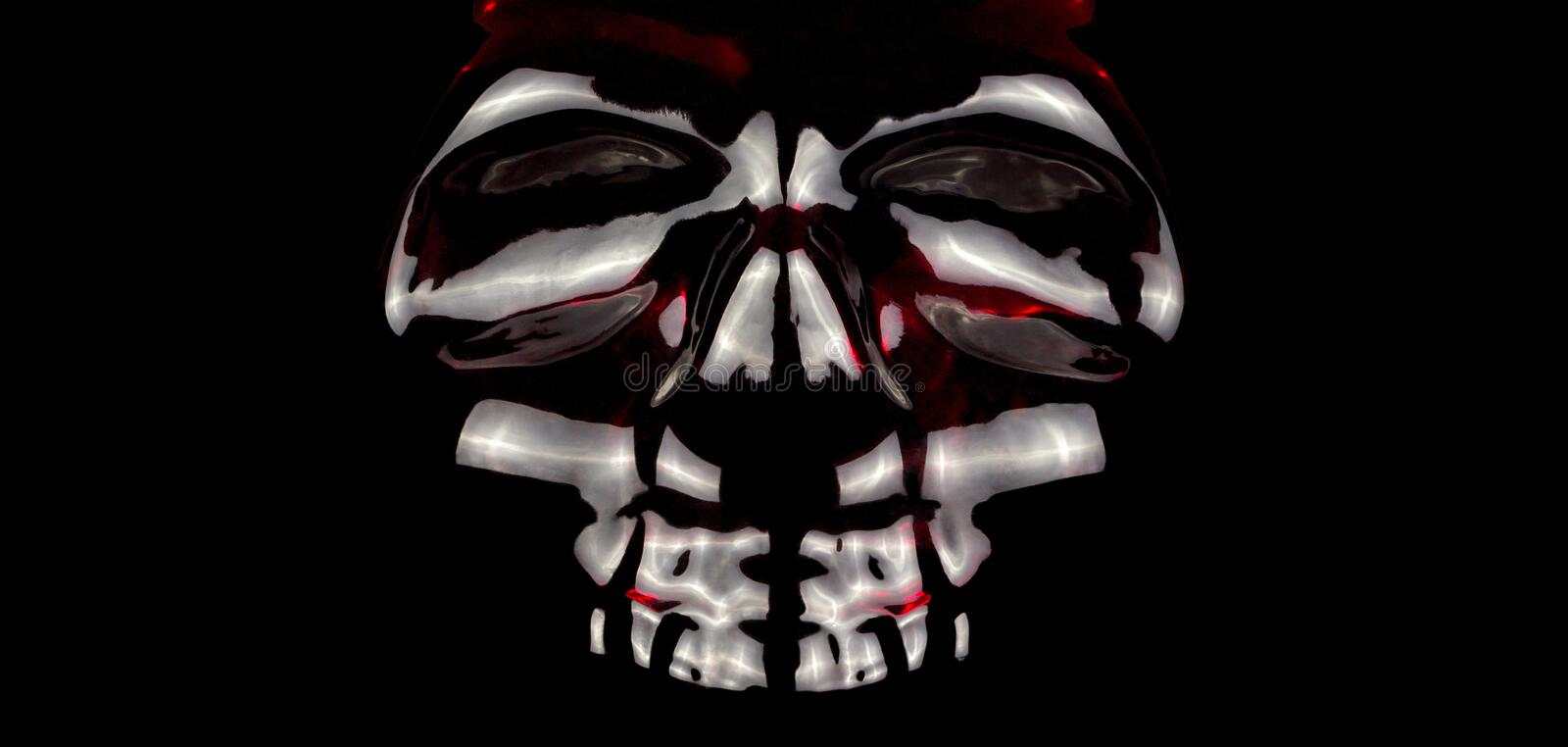 Light reflection from a glass skull with a red glow inside royalty free stock photography
