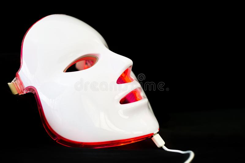 Light rejuvenating mask for facial skin therapy. On black background royalty free stock photography
