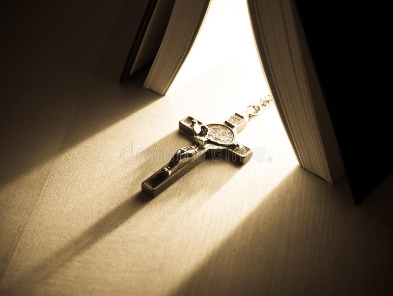 The Light of Religion. Light coming trough a bible shining on a cross royalty free stock photo