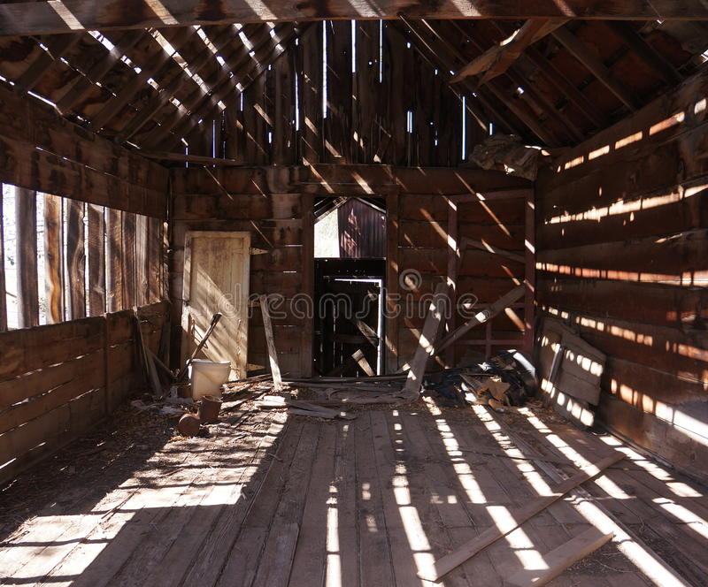 Light and Shade in an Old Shack. Old wooden shack interior with strong patterns of light and shade. These are caused by strong sunlight entering the building stock image