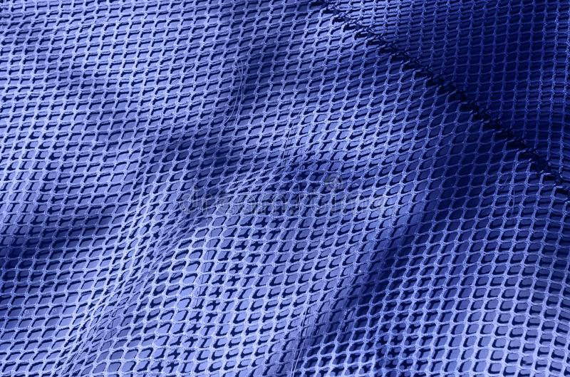 Blue textile grid background. Light and shadow alternate on the chicken wire background royalty free stock photos