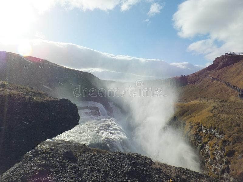 Light and shadow in the mist rising above Gullfoss waterfall in Iceland on a bright sunny autumn day royalty free stock image