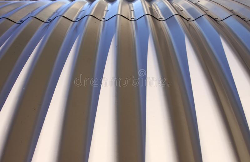 Light and shadow pattern on corrugated metal sheet coverage stock image