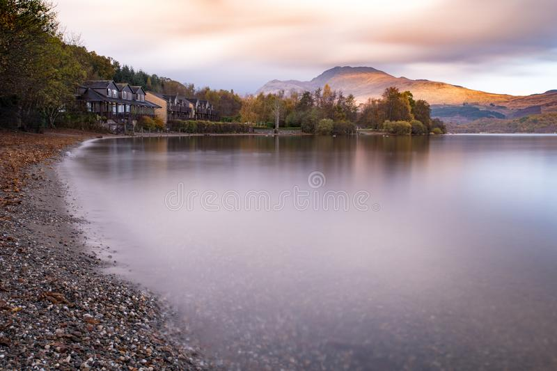 Light shines onto Ben Lomond. Ben Lomond catching some utterly gorgeous light, as seen from the shore at Luss just after the wonderful rainbow in a break in the stock photo
