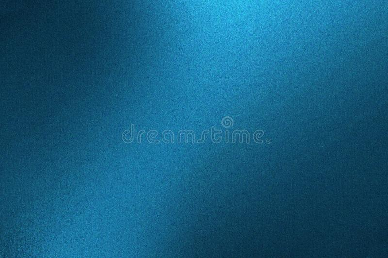 Light shining on blue metallic wall in dark room, abstract texture background stock photo