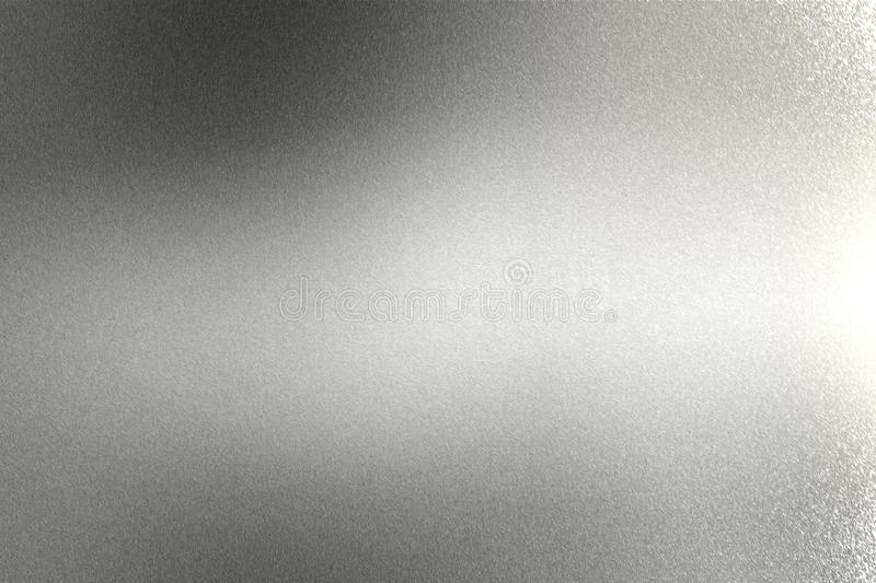 Light shining on brushed silver metal wall texture, abstract background royalty free stock photo