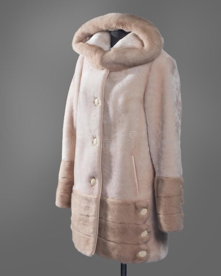 Light short coat straight silhouette of Mouton and mink trim on the edge of the hood and sleeves, slanting pockets with leather. Trim. Vertical frame for the royalty free stock images