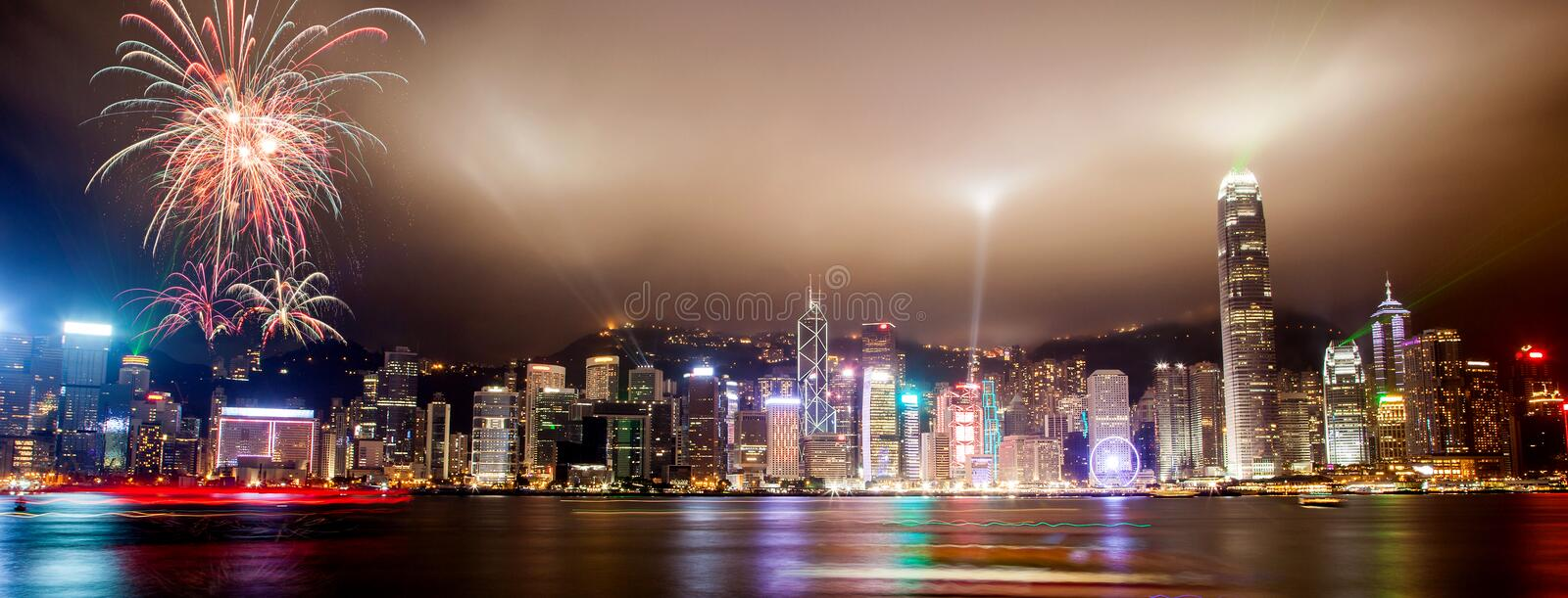 Light Show Over Hong Kong Skyline at Victoria Harbor. Panorama view of Hong Kong skyline with lasers, floodlights and fireworks illuminating the night skies on stock photography