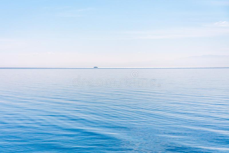 Light and simple landscape with blue sky, light clouds and wavy blue water with a ship in a distance stock photo