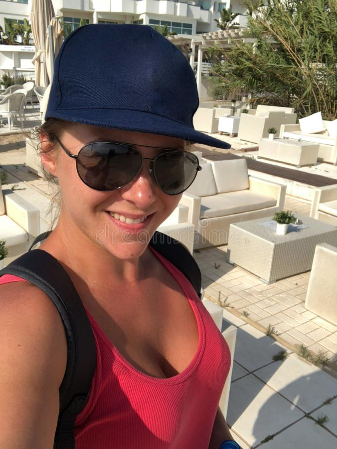 A light-skinned young woman in a cap, sunglasses and a pink t-shirt with a radiant face and beautiful Breasts makes a selfie on. The background of the hotel stock images