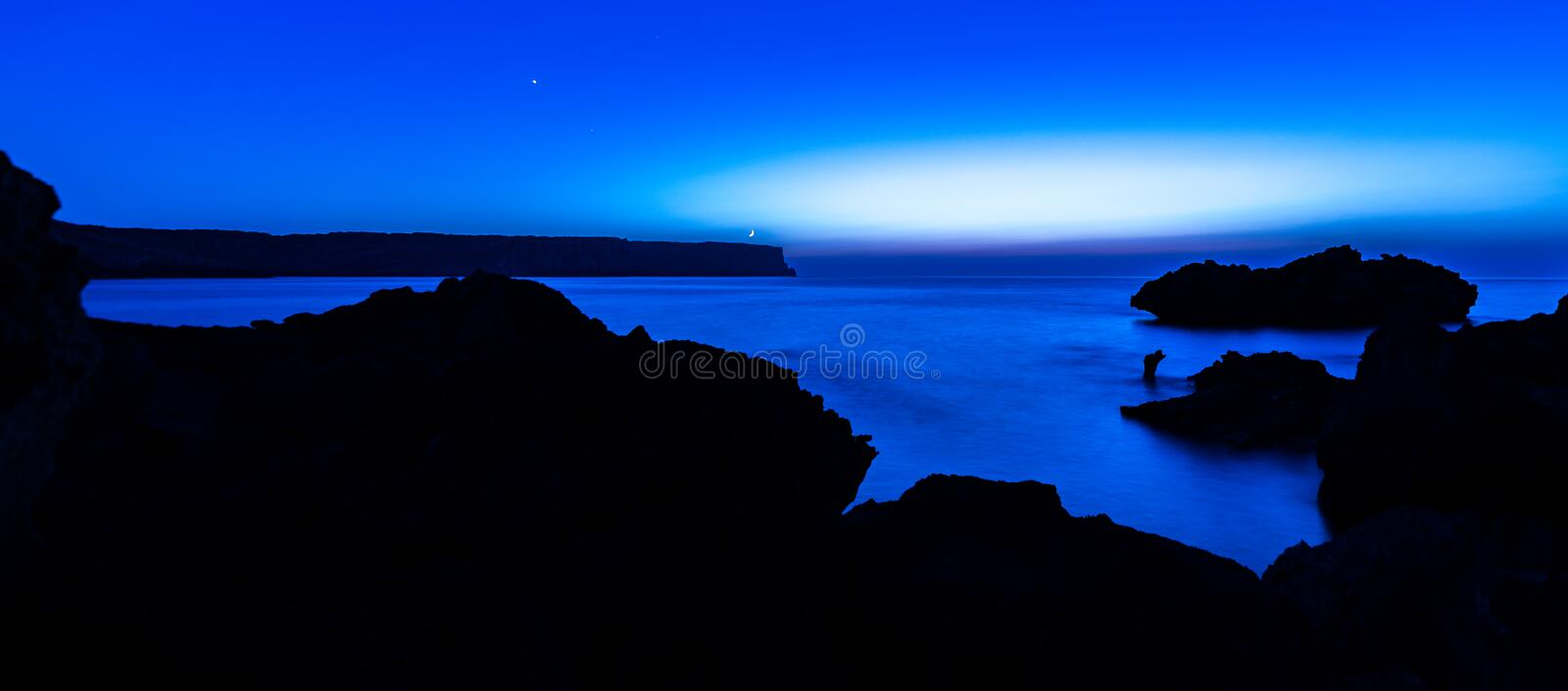The blue night lighthouse. The light of a small lighthouse indicates the path of a cold blue night stock image