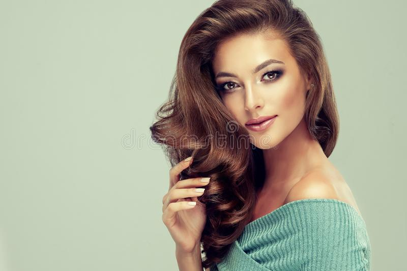Light smile on the face of young, brown haired beautiful model with long, curly, well groomed hair. Excellent hair wav stock photo