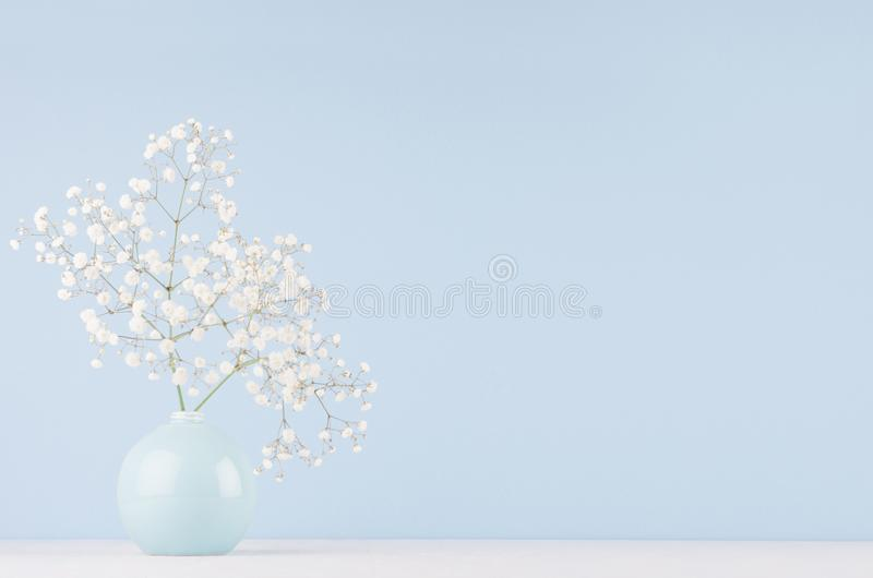 Light soft elegant home decor with small airy flowers in glossy pastel blue vase on wood table and blue wall. Light soft elegant home decor with small airy royalty free stock photography