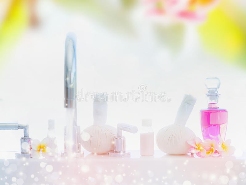 Light spa or wellness background with Bathtub , body care products, massage stamps and frangipani flowers stock photos