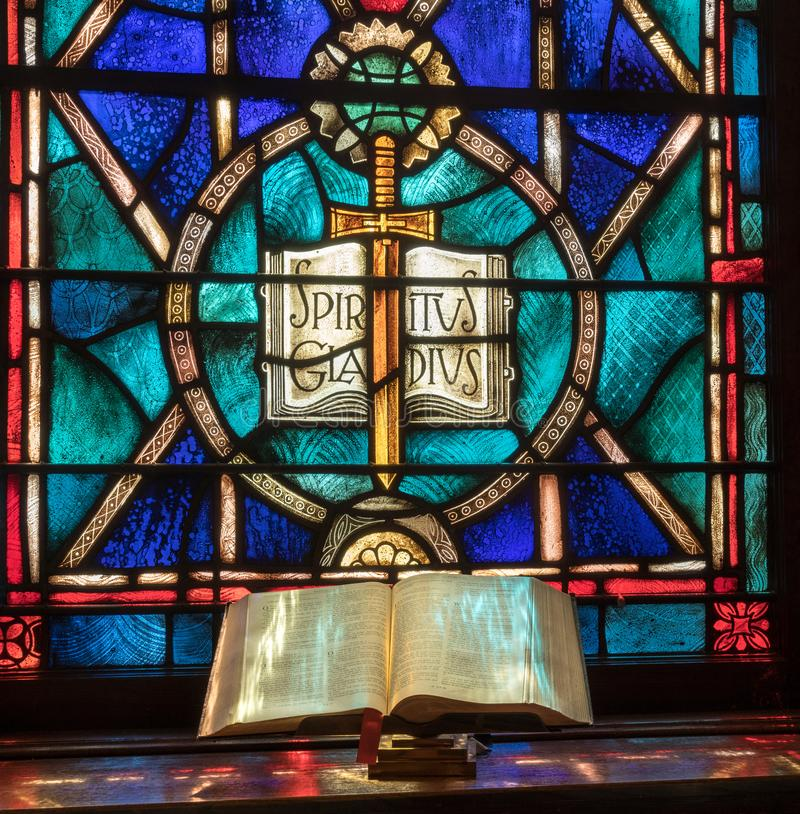 Light from stained glass window falls on open bible in american church stock image