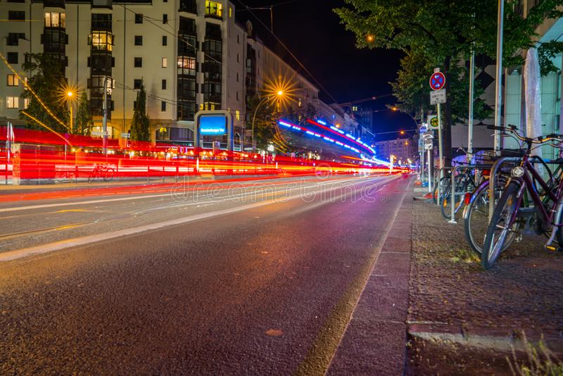 Light streams from passing vehicles reflecting off tram lines down center of road and hire bikes on right. Long exposure night image Friedrichestrasse retail stock images
