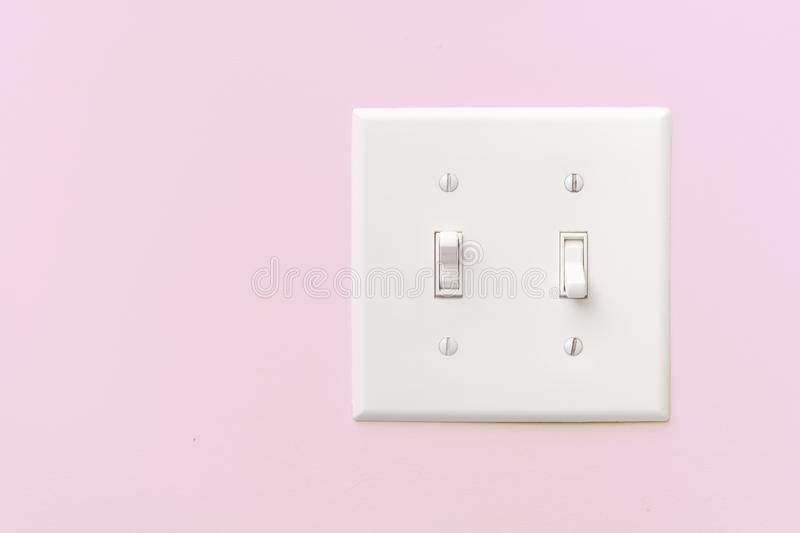 Light Switch. Interior light switch on pink wall with copy space stock photography