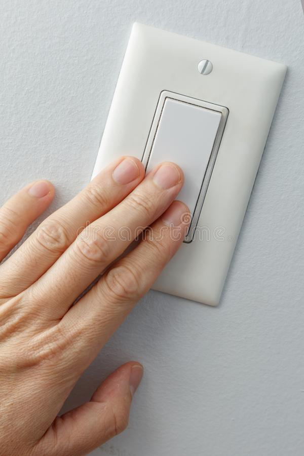 Light switch on or off. Hand turning white light switch on or off royalty free stock photography