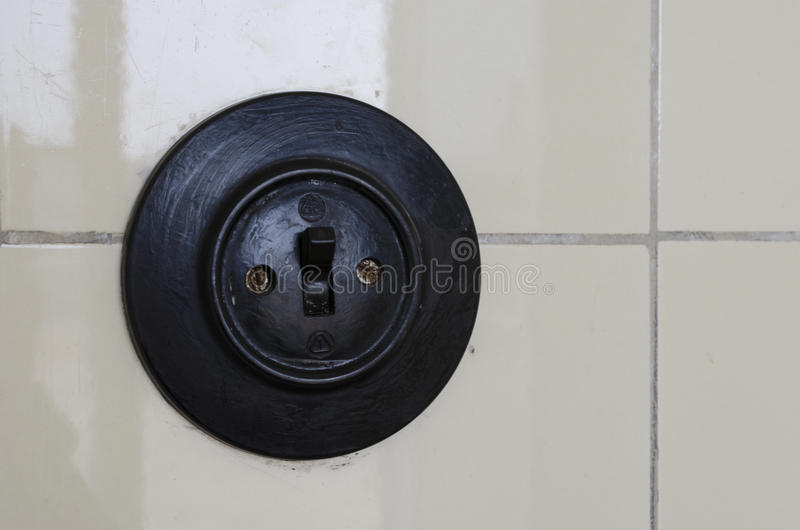 Light Switch. Old fashioned light switch mounted on pale yellow ceramic tiles stock photo