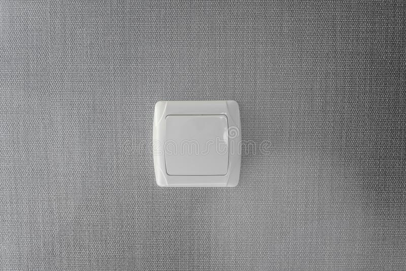 Light switch. Plastic mechanical switch of white color installed on a light gray wall. stock images