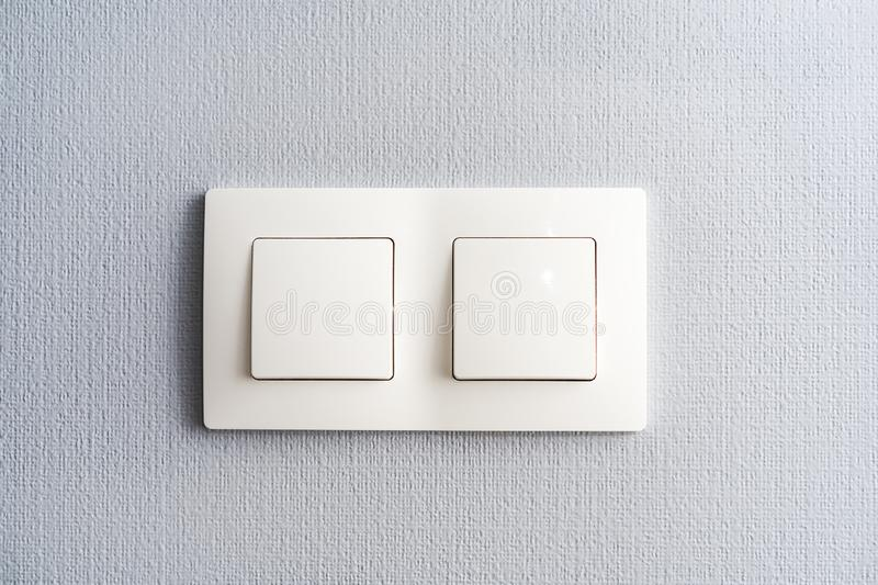 A light switch, a plastic mechanical switch of white color installed on a light gray wall in the room royalty free stock photo
