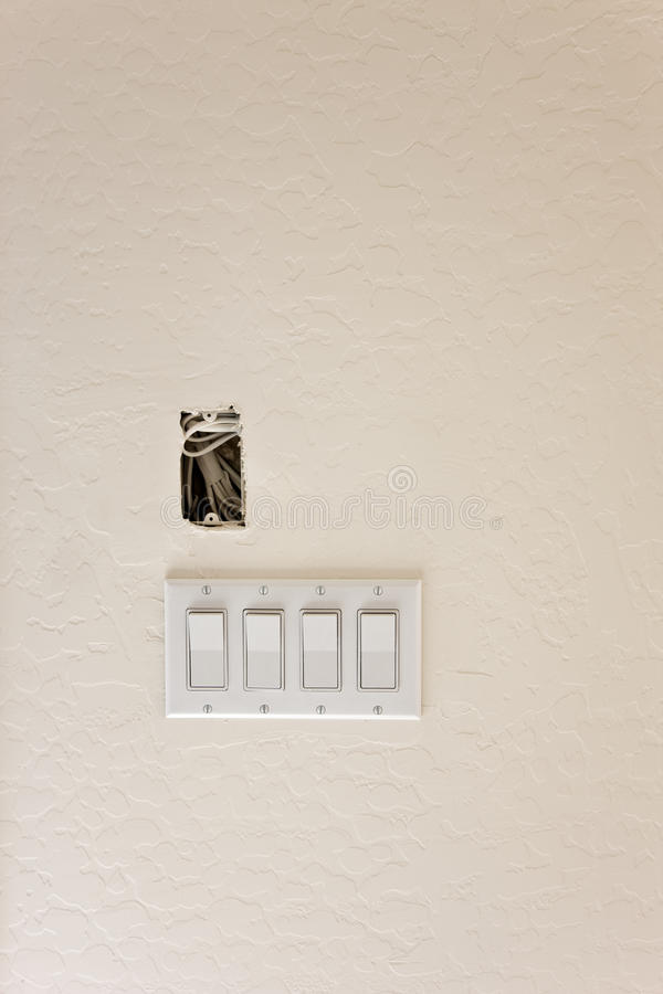 Light Switches in New Construction. Freshly primed drywall with new light switches in a new construction of a house. Image is a high resolution file recorded stock images
