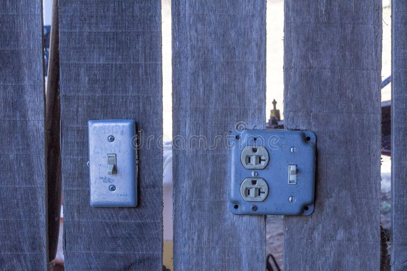 Light switches and outlets mounted to wood wall slats of an old barn. Horizontal aspect royalty free stock photography