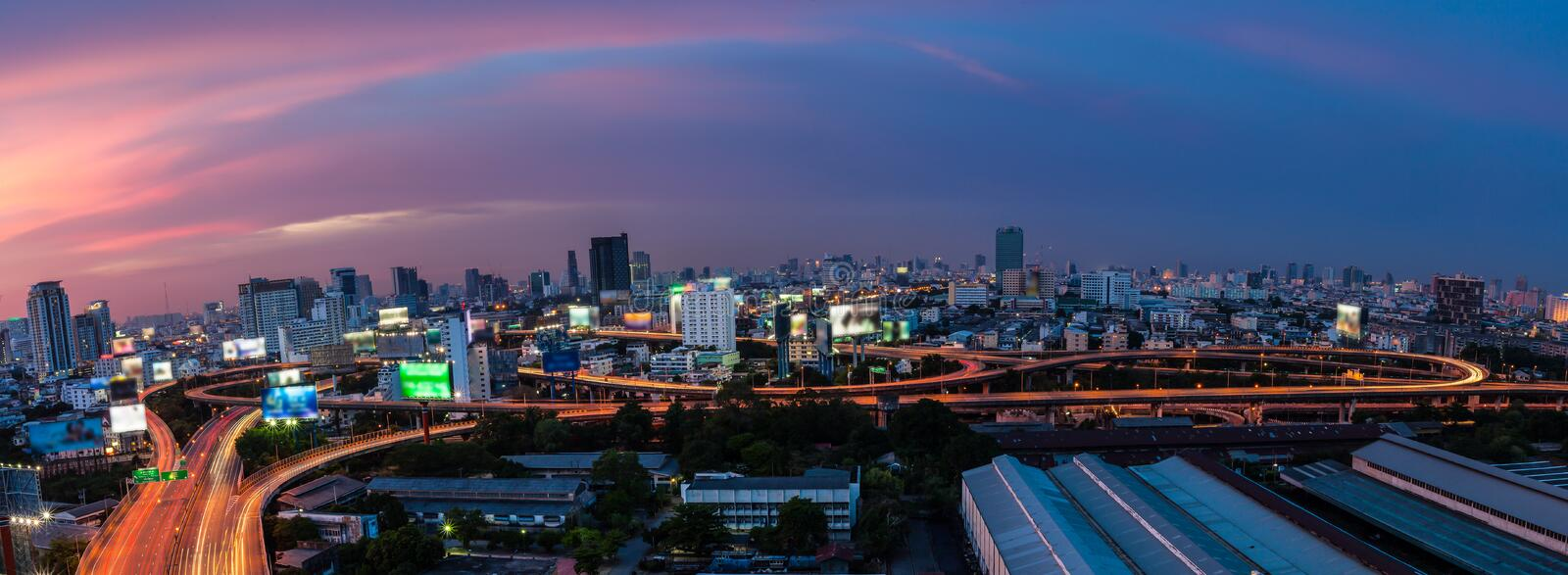 Light tail of Transportation car on road way at night life and B. Usiness Building Bangkok city area background as panorama, high angle birds eye view stock photo