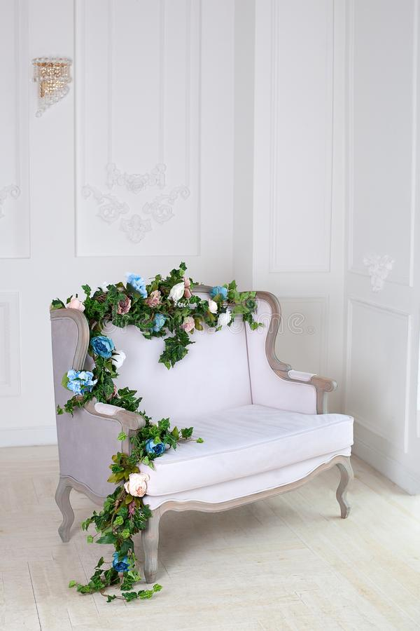 Light textile classic sofa in a vintage room. a light classic royal interior with a soft sofa with a fabric upholstery. Elegant ro stock images