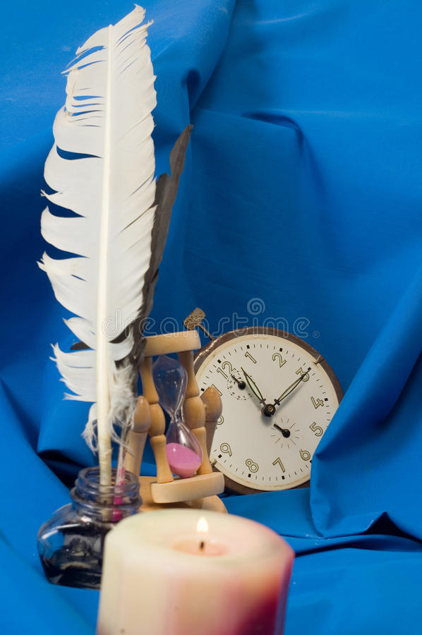 Light and time. Still life of hourclock, clockwork and candle stock photography