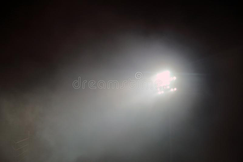 Light tower lit at a stadium during nightime. Stadium lights against dark night sky background. stadium lights and smoke stock photography