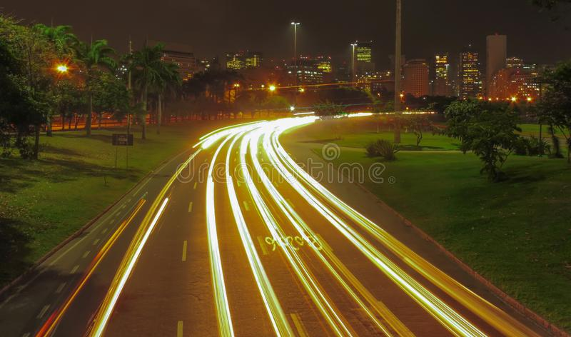 Light Trail at Aterro do Flamengo 2. Photo taken on footbridge at night after rain with the rio de janeiro downtown in the background royalty free stock photo