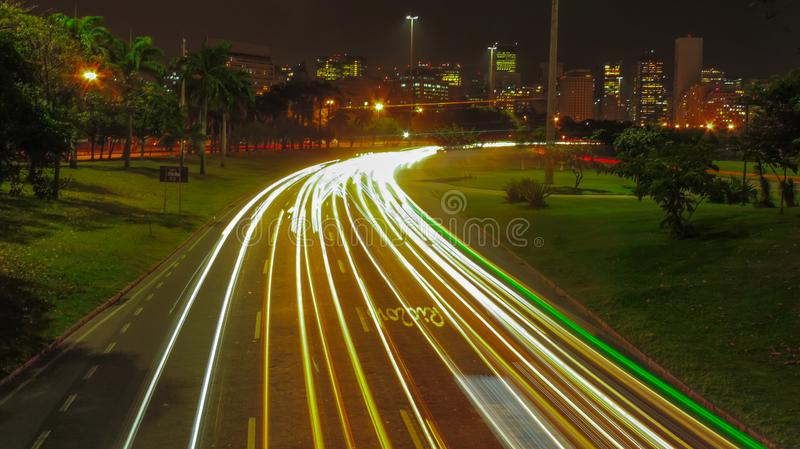 Light Trail at Aterro do Flamengo. Photo taken on footbridge at night after rain with the rio de janeiro downtown in the background stock image