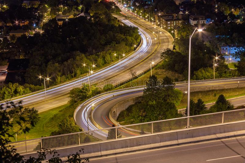 Light trails from cars going around corners at night in Hamilton, Ontario. Cars driving around a corner on the Jolley Cut at night creating light trails on the royalty free stock images