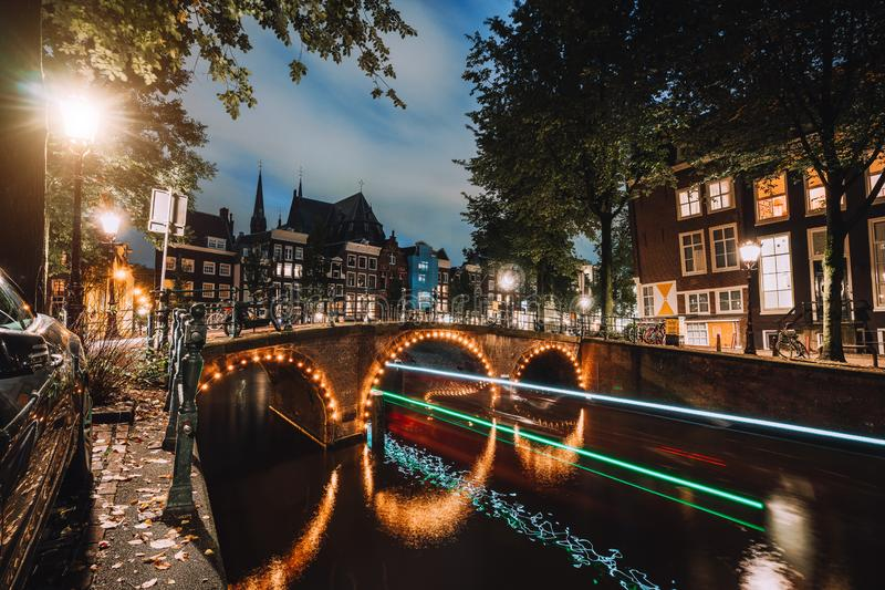 Light trails at famous canals in Amsterdam at dusk. Long exposure shot.  stock photo