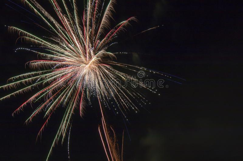 Fireworks on a black canvas. Light trails from a fireworks explosive blast illuminating the black sky long exposure of a firework display on a holiday royalty free stock photos