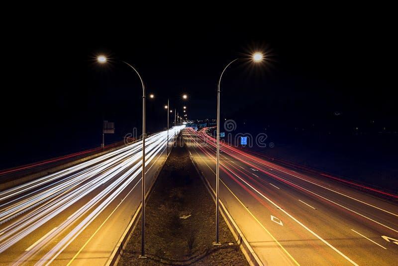 Speed traffic - light trails on highway at night. Cars exiting highway. Light trails on highway at night. Cars exiting highway stock image
